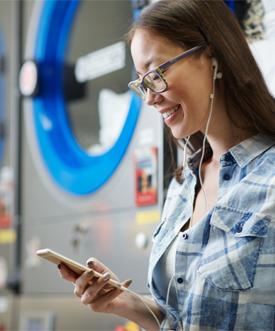 woman listening to music through her headphones inside laundromat